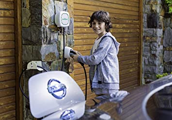 A white Home EV charger made by Wallbox as part of the pulsar plus range. It is attached to a garage and a young boy is charging an electric vehicle.
